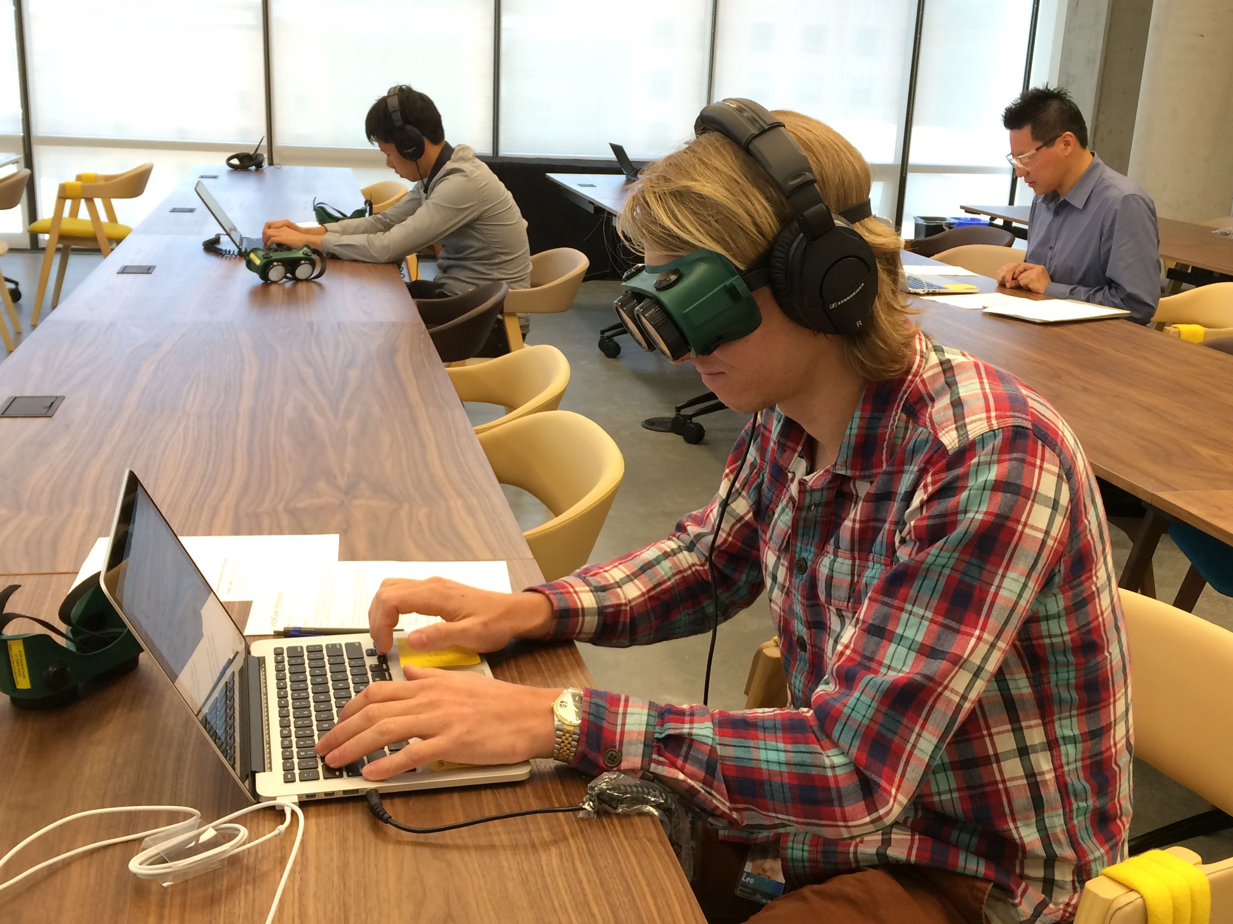 At another Assistive Technology Lab, someone wears headphones and special goggles that obscure their vision while they navigate dropbox.com with a screen reader.
